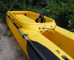 Fishing kayak with paddle holder